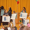 1/23/97 Reading Assembly - James Neiss Photo - Be Excited About Reading - Parents as Reading Partners at the Errick Road Elementary School. PARP Bear greets children with the help of L-R - Matthew Canida 8/3, Derek Kratts 6/kg, Alex Clark 8/3 and David Ceccato 6/kg.