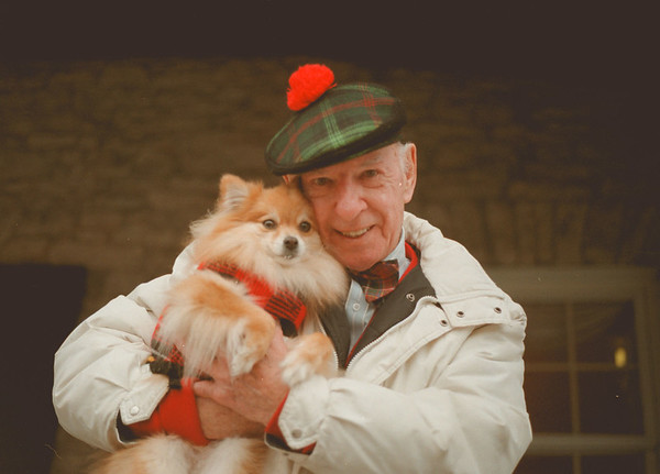 98/01/28--dog & hat-- Katie Kamphuis photo-- Bob Monihan of Niagara Falls holds his dog, Molly, a two year old pomeranian, on Center Street in Lewiston on Wednesday.   He shows off one of his many colorful  hats he owns.<br /> <br /> Grapevine photo