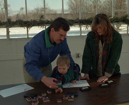 98/02/06 Winterfest 9 *Dennis Stierer photo - Keith and Kristen Wiesinger from Wilson help their son Kevin, 21 months do some stamp pad stamping at the Winter in Nature Exhibit.