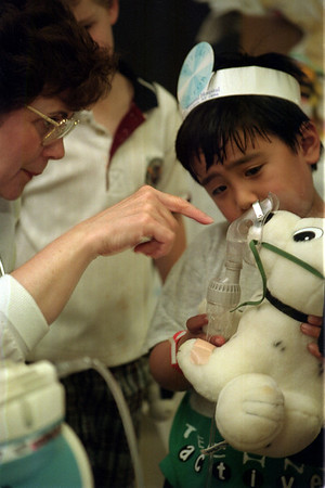 "98/05/15 kids clinic 1-Rachel Naber Photo-Catherine Moran (left) a nurse at Lockport Memorial Hospital dispells N.J. Solis worry about how the oxygen mask works on his favorite dog, ""Rex""."