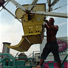 98/08/04 County Fair 3 - James Neiss Photo - Preston Cole of Delaware, a ride operator with Amusements of Buffalo, attaches ferris wheel seat safety devices in preperation for the openig of the Niagara County Fair..