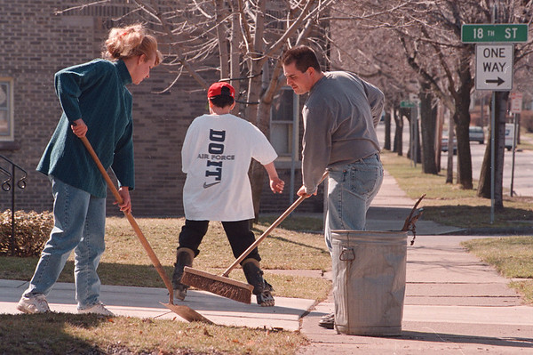 4/2/97--SPRING CLEANING--DAN CAPPELLAZZO PHOTO--MATT RUGGIERO (RIGHT W/BROOM) AND HIS WIFE SHELBY DO A CLEAN SWEEP OF THEIR WALNUT STREET DRIVE WAY AS NEPHEW STEVIE BROWN ROLLERBLADES WITH SPRING LIKE WEATHER IN THE AIR.<br /> <br /> NEWS/LOCAL