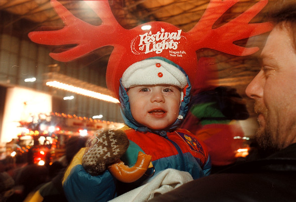 97/11/18-- Festival of Light 96--Takaaki Iwabu photo--From 1996 Festival of Light...... a 19-month-old Cole Tiedemann, Sanborn, sports a foam-rubber antler hat as he and his father John watch Festival of Light's parade in front of niagara Falls Convention and Civic Center. <br /> <br /> Friday, feature, color