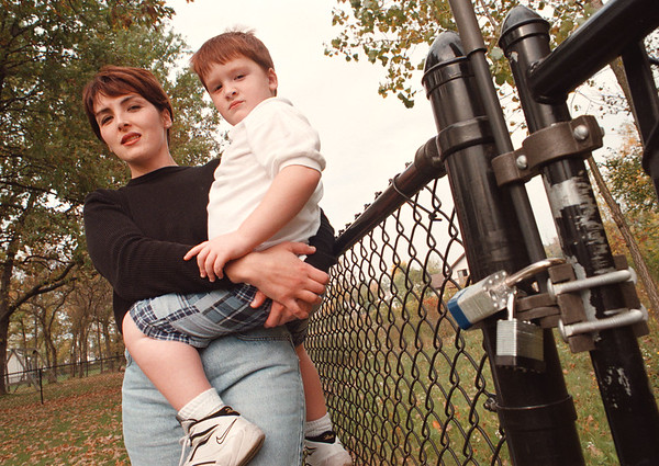 97/10/09--POOL LOCKS--DAN CAPPELLAZZO PHOTO--HEATHER DeCASTRO HOLDS HER 4-YR-OLD SON DAMON NEAR A LOCKED GATE AT THEIR LEWISTON HOME. DeCASTRO HELPED GET A NY STATE LAW PASSED CALLING FOR LOCKS ON SWIMMING POOLS.<br /> <br /> SAT LOCAL