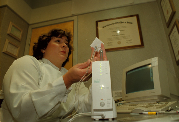 98/08/06 Dental Pain - James Neiss Photo - Kathleen M. Casacci, D.D.S. shows off the device that allows almost painless injections of anesthetic for dental work.