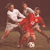 11/4/97 -- Soccer 1--Takaaki Iwabu photo-- Olean HS Val Waldron, right, controls the ball against Lew-Port HS Jessica, Mann, left, and Rosie Luzak.