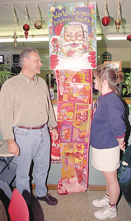 98/12/07 gasport stocking--dan cappellazzo photo--(ltor)ower of the gasport cafe David Schwartz and employee heather torriere stand next to the world's largest stocking.
