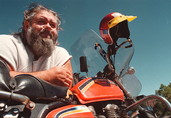 9/4/97-- biker--Takaaki Iwabu photo-- Ray Walker of Ransomville rests on his bike at the parking lot of Niagara Falls Library. He rides his Honda almost everyday to visit the Library for books and movies, he said. <br /> <br /> grapevine photo