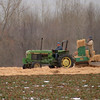 98/02/03 Straw-Berries*Dennis Stierer - During the wintertime, strawberries need to be protected from the wram and cold spells, so straw is used to cover the berries till spring. Don Collins drives, while Jeff Hall loads straw in the spreader. This field of strawberries is owned by Jim Coulter Farms.