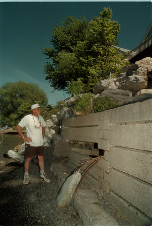 98/05/24 Olcott Water - James Neiss Photo - Bob Pleger of 5967 Ontario in Olcott, 778-9747, looks over the more than 208 tons of stone that cost over $6000.00 to fill in a erosion hole spanning more than 32x12x18 in his back yard. The water level also damaged the break wall infront of him.