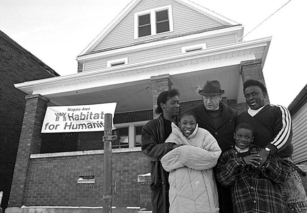 1/19/97--NEW HOME--CAPPY PHOTO--REV. DAVID DODGE, PRES. OF HABITAT OF NIAGARA (CENTER W/HAT)  STANDS WITH THE WALKER FAMILY; MARY HOLDS HER DAUGHTER MONTRESE, 9, AND RUPERT GEORGE HOLDS HIS SON JOSHUA 8 IN FRONT OF THE NORTH AVE HOME.<br /> <br /> GR