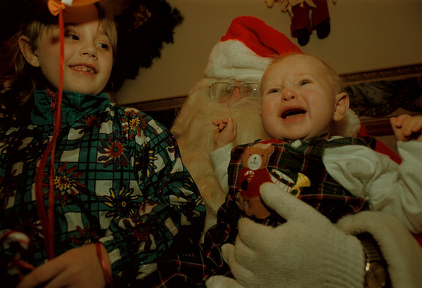 97/12/07--Santa Clause--Takaaki Iwabu photo-- Chloe Harper, 7, left, and her 7-month-old brother Ian Harper show different expressions as they sit on Santa Clause lap Sunday at Historic Post Office. (As part of Christmas Time In The City program.... ) <br /> <br /> For Lockport, color