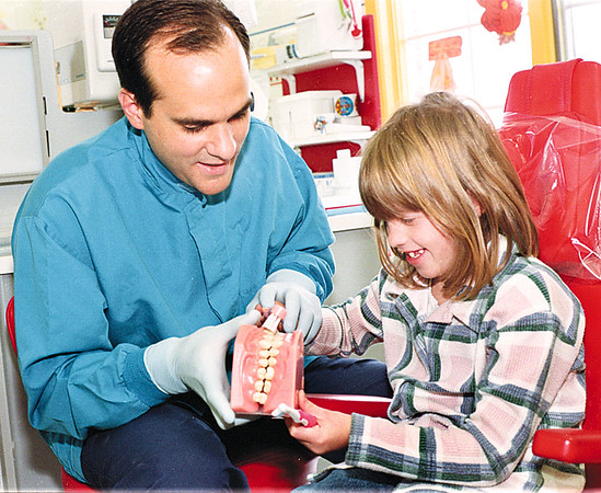 98/11/06 Brush, Brush, Brush *Dennis Stierer Photo -<br /> Dr. Louis A. Surace, a pediiatric dentist in Lockport goes over brushing with patient, Sara Tagg, 8.