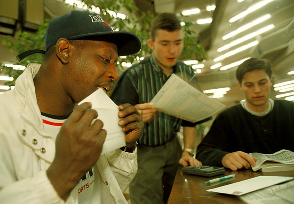 4/15/97-- tax return-- Takaaki Iwabu photo-- From left to right, Charles Packer of Niagara Falls seals an envelop as he gets tax return form done with help of Niagara University students Sean Mcmahon and Adam Wright.