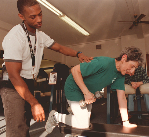 98/02/25--FITNESS 3--DAN CAPPELLAZZO PHOTO--YMCA INSTRUCTOR MICHEAL DAVIS HELPS GASKILL 7TH GRADE TEACHER  MAY JOWDY WITH A TRICEPT KICKBACK LIFTING EXERCISE AT THE PORTAGE RD YMCA.<br /> <br /> FEATURE