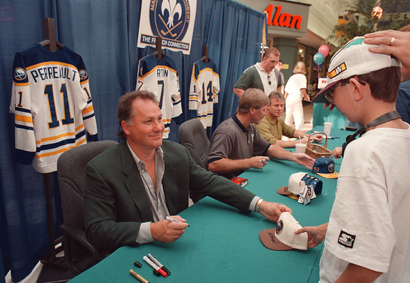 97/09/28--FRENCH CONNECTION--DAN CAPPELLAZZO PHOTO--FORMER SABRE SUPERSTAR GIL PERRAULT SIGNS A HAT FOR 14-YR-OLD JASON BOYE, OF SLOAN AT THE FACTORY OUTLET.<br /> <br /> SP