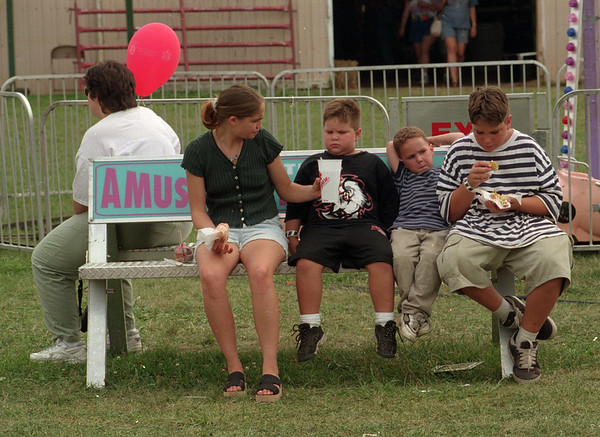 "98/08/07 County Fair - James Neiss Photo - ""Hangin at the Fair"". Here, L-R, Fair goers take a rest, Dee Foote, with baloon, Carla Spencer 20yrs, Nephews Anthony Lechner 6, Christ0opher Lechner 4yrs and brother Nicholas Spencer 11yrs, enjoy their rest."