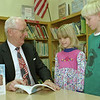98/03/04 Author Visit *Dennis Stierer photo - Students in Mrs. Taber's 2nd grade and Mrs. Schleem's special ed class were treated by having a local guest author, Mr. Wilbur Dunn.  Mr. Dunn shared facts on Abraham Lincoln and on the civil war. Here we see him showing students  Emily Smith and Matt Kelkenberg his book about this period in history.