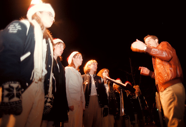 98/12/04 Petersen's Drugs 1- Vino Wong Photo - Phillip Quinn conducts the Newfane High School jazz choir during the 12th Annual Tree Lighting at Petersen's Drugs, Newfane, Friday.