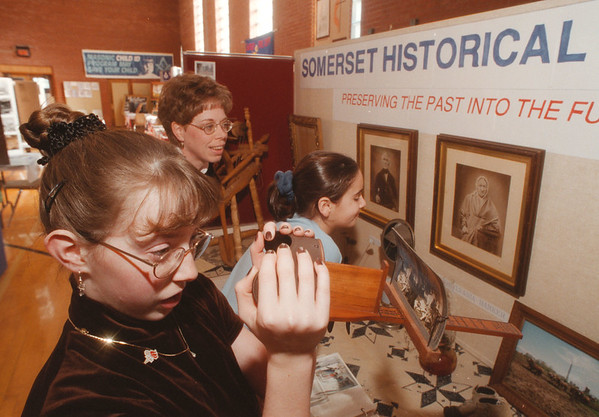 98/02/08 Somerset 175th 2 - James Neiss Photo - L-R - Vanessa Staples 11yrs/6th grade, her mom Cindy Staples and friend Shawna Weis 10yrs in 5th grade look over the Somerset Historical Society booth during the Town of Somerset 175th Anniversary activities at the Barker school system facilities.