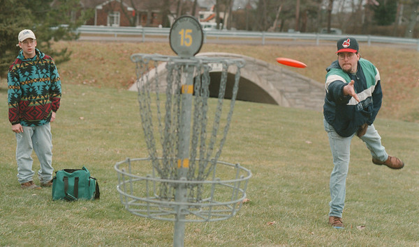 """98/01/03--disk golfers --Takaaki Iwabu photo-- Chris Graziano, right, aims a frisbee as he and his partner Mike Nelson join """"El Nino Disc Golf Tourney"""" Saturday at Joseph Davis State Park in Lewiston. About 20 players from as far away as Hamberg and Buffalo played the Tournament.  --weahter feature, stand alone, local, bw"""