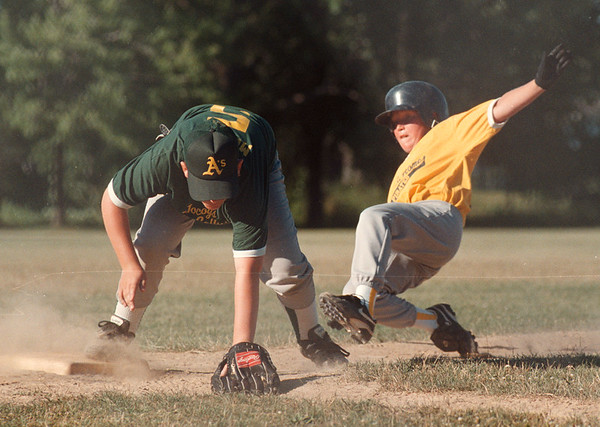 7/16/97-- little league 2--tak photo-- Marcus Murphy, third-baseman for A's manages to catch the ball as Justin Cornelius of Pirates slides into the base.