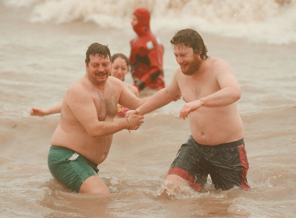 98/03/08-- Polar Bear--Takaaki Iwabu photo-- Mark Budwey, left, and George Henry, both from North Tonawanda, plunge themselves into Lake Ontario during the annual Polar Bear Swim at Olcott Beach Sunday. About 200  swimmers braved the Sunday's rainy and windy weahter. <br /> <br /> 1A, color, Monday
