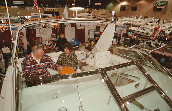 98/02/07--BOAT SHOW--DAN CAPPELLAZZO PHOTO--US COAST GUARD CAPT. BILL SAVAGE AND HIS WIFE LINDA SIT AT THE HELM OF A 37FT SEA RAY SUNDANCER AT THE NFCC WNY BOAT SHOW.<br /> <br /> 1A