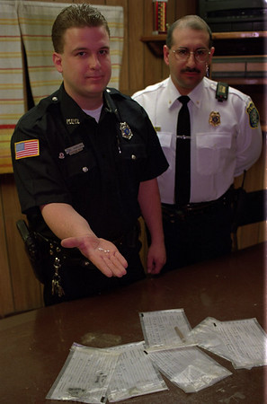98/04/08 Drug Bust *Dennis Stierer photo - Officer Eric T. Harling holds some crack that was seized during a drug bust. Standing behind is Medina Chief Jose' L. Avila.