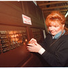 4/17/97 SPCA Doors 2 - James Neiss Photo - Anne Chiodo, public relations specialist with the SPCA affixes a plaque to a garage door in the loby to show off the names of people donating funds for the kennel garage doors.