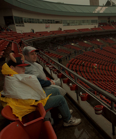 98/04/09--BISONS RAIN--DAN CAPPELLAZZO PHOTO--PAT HOWARD AND HIS SON PAT JR., OF ORCHARD PARK, WAIT FOR THE RAIN TO STOP AT THE BISON RAINED OUT HOME OPENER. THE GAME WAS CALLED AFTER A ONE HOUR WAIT.<br /> <br /> 1A