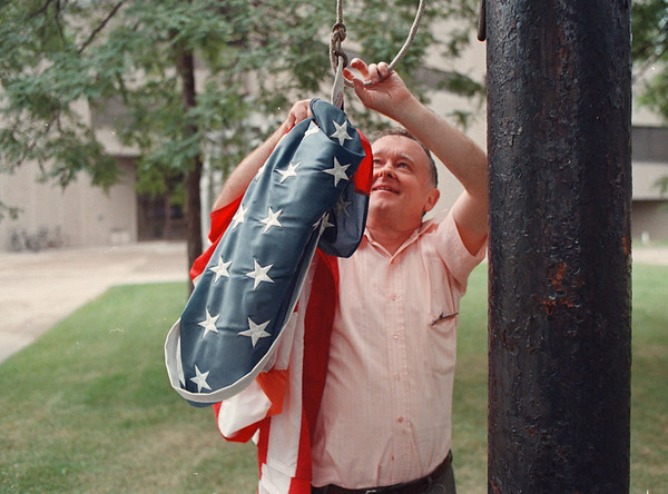 97/09/17 national flag--Takaaki Iwabu photo-- Walter Kelley, a cleaner at Niagara Falls Public Library, takes down the national flag in front of the Library Wednesday afternoon when the rain started. <br /> <br /> Grapevine photo