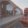 7/15/97 Outlet Mural - James Neiss Photo - Eric Grohe, Mural artist, stands in front of a mural he painted on the Factory Outlet Mall which was unveiled today.