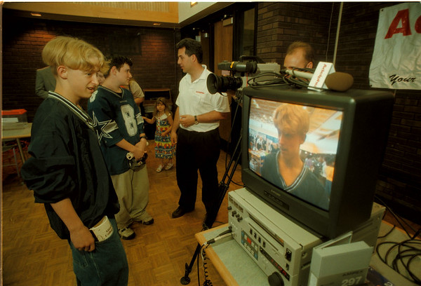 98/05/27 Job Fair - James Neiss Photo - L-R - Joe Conger 14yrs/8th grade admires his video presence as classmate Ed Goodearl, 15yrs/8th grade, talks to Lou Paonessa, Program & Community Affairs Director at Adelphia Cable in NF., about a career in broadcasting. Behind the camera is Production Assistant mark Traina also of Adelphia.