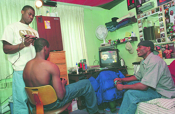 1/23/97--WINN/DORM 2--CAPPY PHOTO--TIM WINN RELAXES BEFORE THE NU GAME WITH DORMMATE DAVID CAPERS AS HE TRIMS THE HEAD OF TEAMMATE CASWELL CYRUS.<br /> <br /> SP