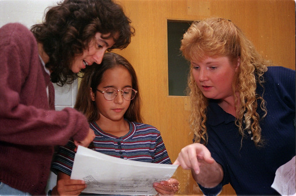 "98/09/03 6th Grade Sucess-Rachel Naber Photo-Bonnie Lugo (left) assists her daughter Ashley Lugo who is ""a little nervous"" as an incoming 6th grader in reading her class schedule and a map of the Medina Wise Middle School as Melissa Schening (right) looks over her shoulder to see if her daughter has the same math class."