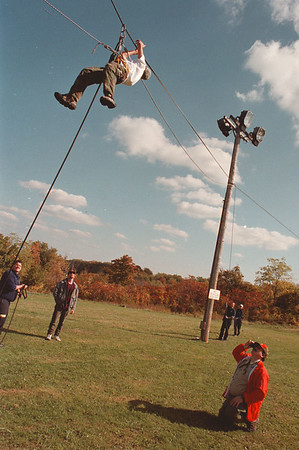 97/10/18--BOY SCOUTS--DAN CAPPELLAZZO PHOTO--14-YR-OLD TEDDY PEREZ, OF TROOP 42, BFLO. WORKS HSI WAY A CROSS A REPELLING LINE 20 FT OFF THE GROUND AS HIS FATHER TED PEREZ (BOTTOM RIGHT) LOOKS ON AT A SCOUT RETREAT AT BOND LAKE, LEWISTON.<br /> <br /> 1A