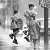6/14/97-- dancing in rain-- Takaaki Iwabu photo-- From left, William Fournier, Michael Rozanski and Michelle Rozanski jump in the air and laugh with joy while sudden rain drenches them on Main Street Friday. Looking on them (from safe area--under roof) is William's fater. <br /> <br /> grapevine photo