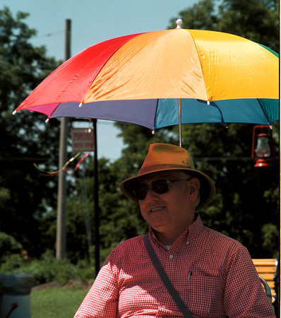 98/07/26 Coool Thing 1-Rachel Naber Photo-Jack Krause keeps cool in Marilyn Tooley Park with his umbrella chair as he watches a human chess game.