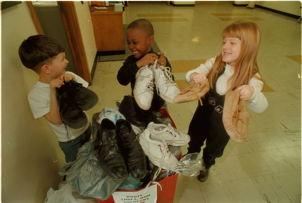 98/02/26 Shoe Donation - James Neiss Photo - Michael Ciraolo 5, Dominique George 5 and Chandra Knotts 6yrs, shows off some of the shoes that the G. J. Mann Elementary School is donating to the needy.