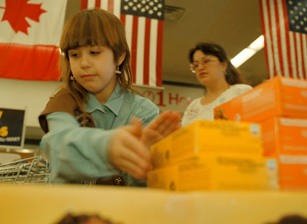 98/03/09-- scout cookies--Takaaki Iwabu photo-- Angel Thomas, a 8-year-old girl scout sets up a table with her mother Rose, back, before their Troop sell cookies at Wal Mart in Niagara Falls. (They are from Troop 267 of  Fallsview Girl Scout) <br /> <br /> grapevine photo