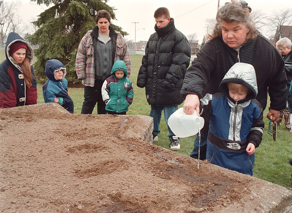 4/18/97 -- seeds for hope --Takaaki Iwabu photo-- Mitzie Daugherty, right, helps her son Eric putting water on the seeds they planted during the Memorial Ceremony for children who perished in the Okalhoma City Bombing. Parents and children from Head Start and area's politicians get together in Hyde Park Saturday for the ceremony.    --1a, Sunday