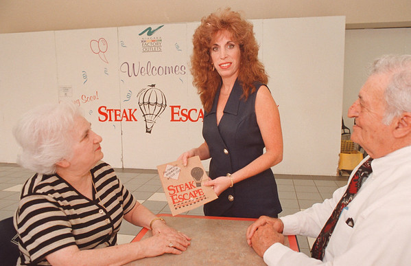 6/13/97--STEAK ESCAPE--DAN CAPPELALZZO PHOTO--LINDA BRUNO HOLDS A BAG FROM THE STEAK ESCAPE AS HER MOTHER AND FATHER SIT ROY AND MEGA (CORRECT SPELLING) SPINA, OF LEWISTON, LOOK ON AT THE LOCATION IN THE FACTORY OUTLET FOOD WHERE THEIR BUSINESS WILL EB.<br /> <br /> $$ PG