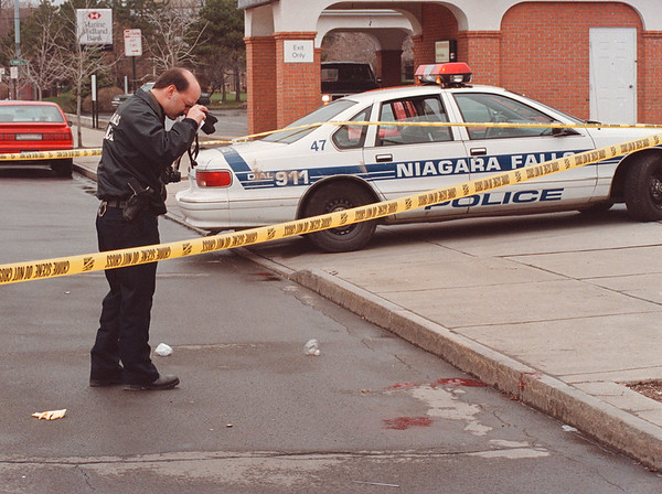 4/17/97 Fatal Shooting - James Neiss Photo - ID Officer Joseph Paul photogrphs the sceen of a fatal shooting on Pine between 10th and Portatge. Notice the butter knife at bottom center.