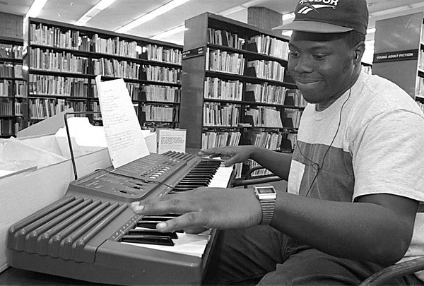 1/8/97--LIBRARY MUSIC--CAPPY PHOTO--LOCAL MUSICIAN HULONDA MOORE, OF THE NIAGARA FALLS BAND DYNAMIC SOUND, WRITES A SONG AT HE NF LIBRARY WIHT THE HELP OF A PAIR OF HEADPHONES. MOORE HOPE TO SAVE ENOUGH MONEY TO TAKE HIS MUSIC AND HIS DREAM TO DETRIOT TO HIT THE BIG TIME.<br /> <br /> GR