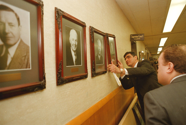 98/01/12--SUPREME COURT--DAN CAPPELLAZZO PHOTO--ATTORNEY DAVID BONIELLO LOOKS ON AS NF SUPREME COURT CHIEF CLERK ANGELO DelSignore hangs portraits of all the niagara county supreme court judges from 1906 to present.<br /> <br /> local