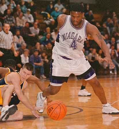 2/5/97--NU BASKETBALL--DAN CAPPELLAZZO PHOTO--NU'S JERMAINE YOUNG BEATS TWO CANISIUS PLAYERS (ON GROUND) IN FIRST HALF ACTION AT THE GALL. CENTER.