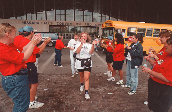 97/08/20 United Way - James Neiss Photo - Chris D'Aloise, a volunteer from Moore Business Forms, center, is greeted by bubbles, cheers and handshakes from United Way staff after getting off a bus from volunteering on a clean up project somewhere in the county.