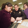 "1/28/97 Science & Math Night 2 - James Neiss Photo - LewPort North Elementary Science and Math Night - L-R - Gina Munno 8/3rd, Lewiston Police Chief Ronald Winkley, Becky DiFiore 3/9 and Katie Rossi 10/4 perpair to get their finger prints for a math project. ""Are you a loop, Whorl of Arch?"""