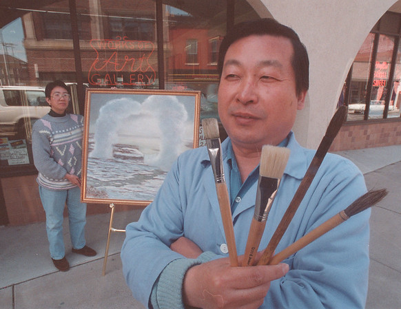 4/18/97 Falls Artist - James Neiss Photo - Xijie Hou (C.J.) Owner of Works of Art Gallery and artist Zhuqing Fucha with a sample of his Falls work.